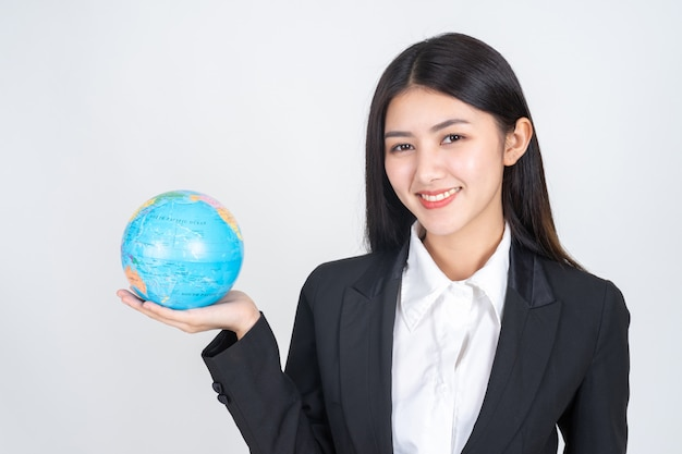 Junge frau des erfolgreichen schönen asiatischen geschäfts, die in der hand weinlesekarte der kugelweltkarte hält