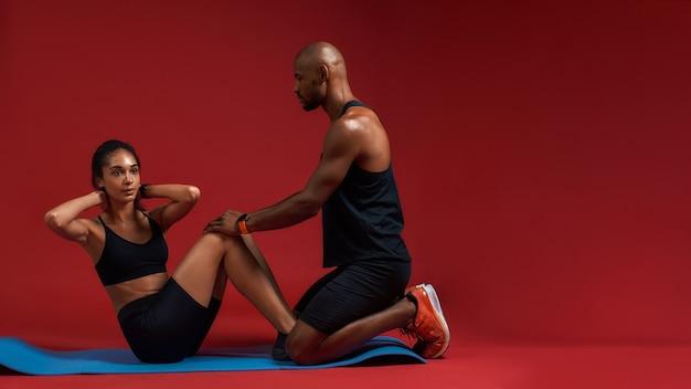Junge frau des fitnesstrainers, die auf der matte liegt und sit-ups mit hilfe von macht