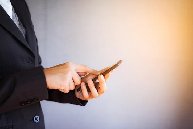 Junge frau des geschäfts, die smartphone im büro verwendet.