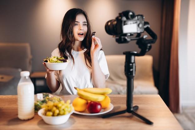 Junge frau des gesunden lebensmittelbloggers, die frischen veganen salat im küchenstudio isst, tutorial vor der kamera für videokanal filmend. weibliche influencerin zeigt kein junk food, spricht von gesunder ernährung.