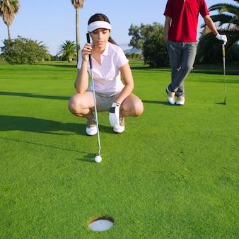Junge frau des golfs, die das loch schaut und zielt