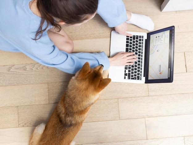 Junge frau des hohen winkels, die neben ihrem hund an ihrem laptop arbeitet