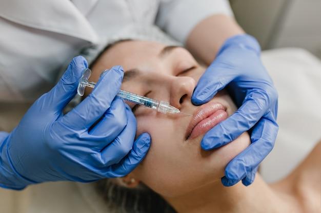 Junge frau des nahaufnahmeporträts, die botox-verfahren durch fachmann tut. injektion, lippenherstellung, moderne geräte, technologie, medizin, kosmetiktherapie