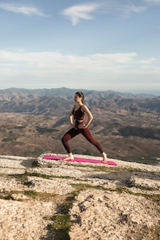 Junge frau des niedrigen winkels auf dem berg, der yoga tut