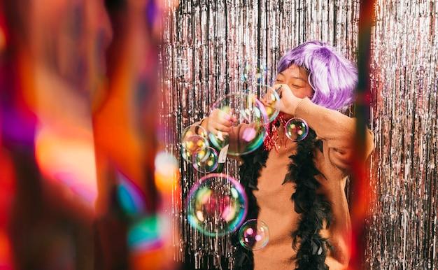 Junge frau des niedrigen winkels mit perücke an der karnevalsparty