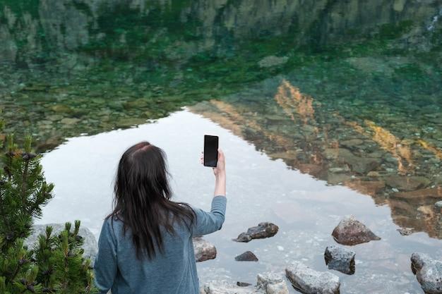 Junge frau des reisebloggers, die am seeufer steht und foto macht