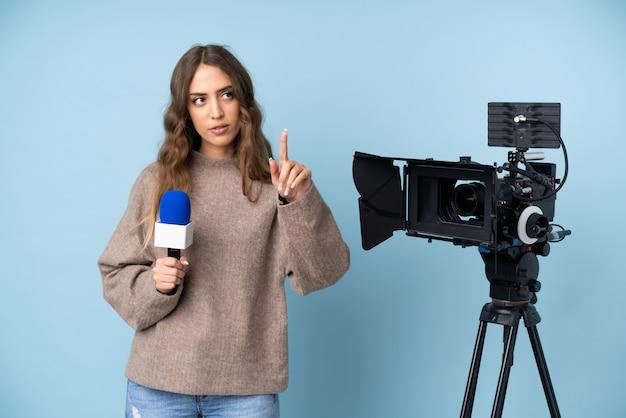 Junge frau des reporters, die ein mikrofon hält und die nachrichten berührt auf transparentem schirm meldet