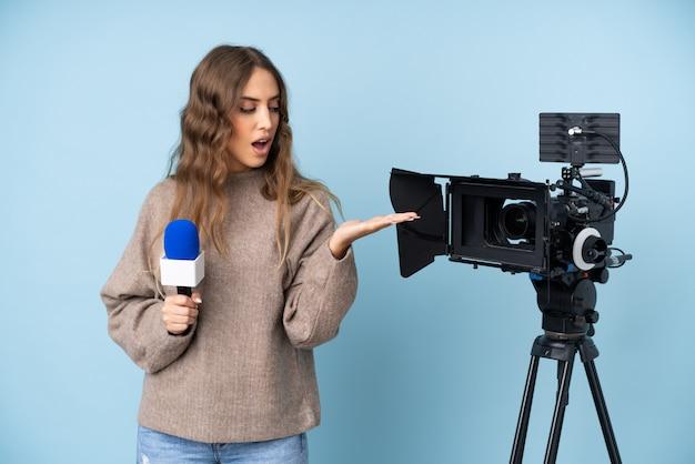 Junge frau des reporters, die ein mikrofon hält und die nachrichten hält copyspace eingebildet auf der palme berichtet
