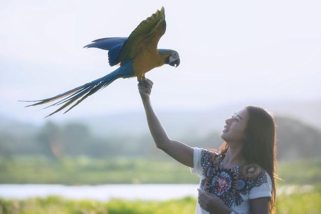 Junge frau des schattenbildes mit lustigem buntem papageien