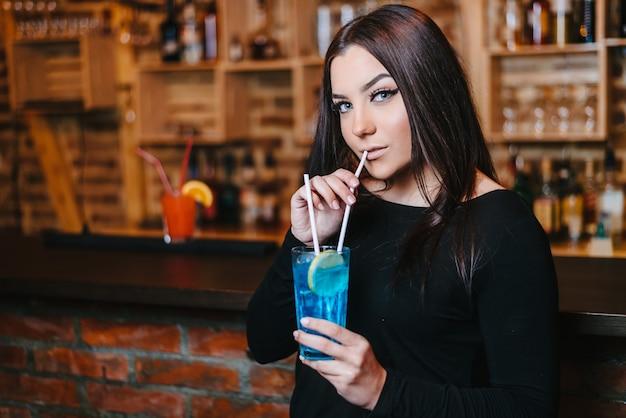 Junge frau des schönen attraktiven brunette, die blaues lagunencocktail im nachtclub trinkt.