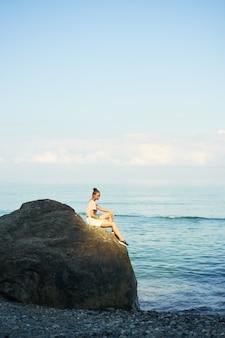 Junge frau des schönen reisenden, die auf steinküste mit rucksack sitzt und ansicht des seesommers genießt