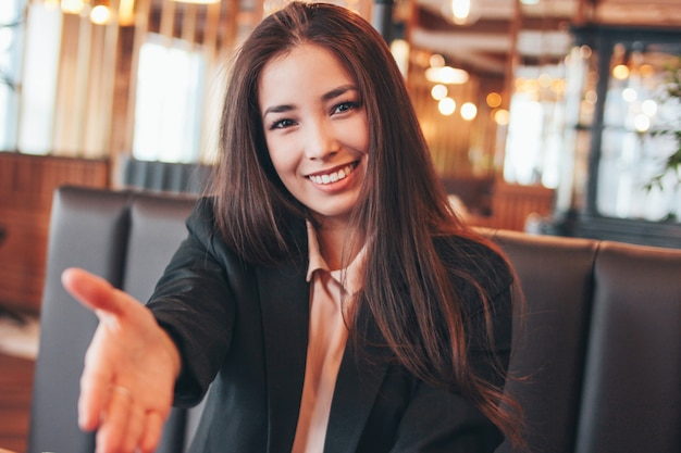 Junge frau des schönen reizenden brunette glücklich asiatischen, die händedruck gibt