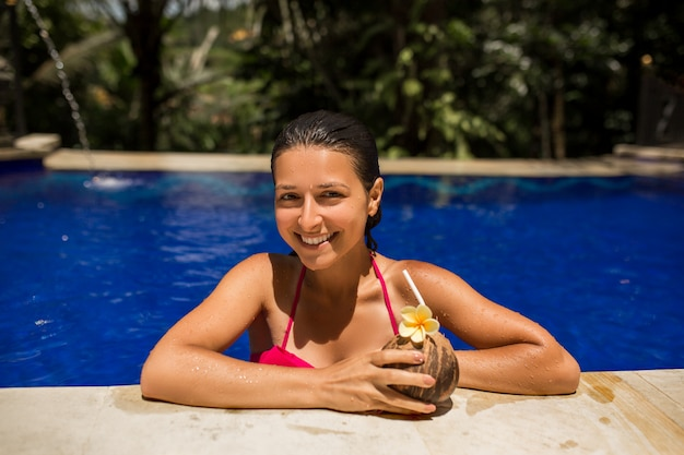 Junge frau des sexy dünnen brunette, die mit frischer kokosnuss im pool mit blauem kristallwasser aufwirft