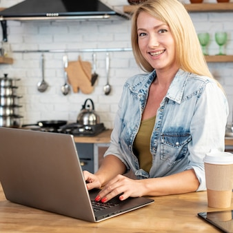 Junge frau des smiley, die an einem laptop arbeitet