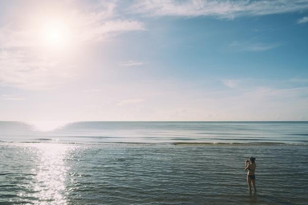 Junge frau des sommerstrandes, die auf dem sand steht und fotos in phuket, thailand macht.