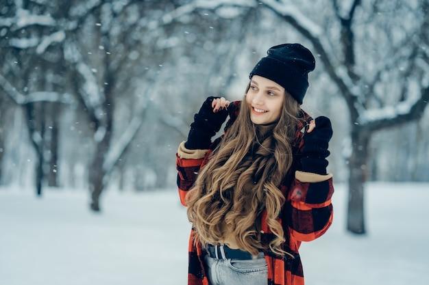 Junge frau des winters porträtschönheit fröhliches modellmädchen, das im winterpark lacht und spaß hat