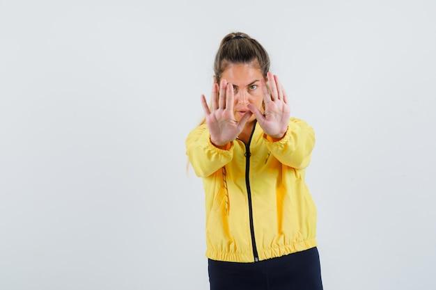 Junge frau, die ablehnungsgeste im gelben regenmantel zeigt und ernst schaut