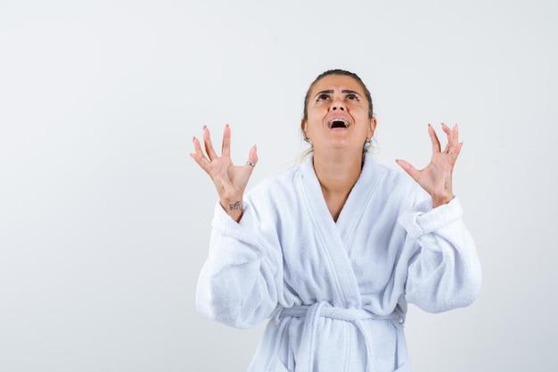 Junge frau, die aggressiv die hände im bademantel hält und genervt aussieht