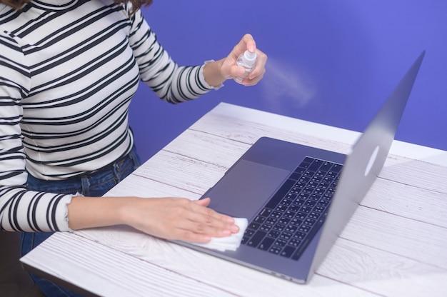 Junge frau, die alkoholspray mit computer desinfiziert, kovid-19-schutzkonzept.