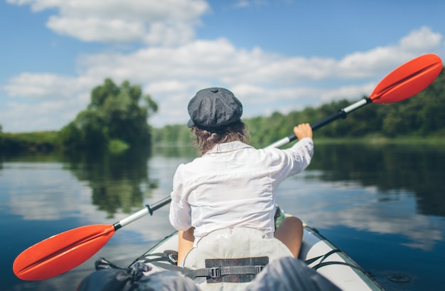 Junge frau, die allein auf einem fluss ohne sicherheitsweste kajak fährt. alleine reisen. urlaubszeit draußen. schöne natur und sonniger tag.