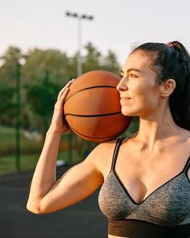 Junge frau, die allein basketball spielt