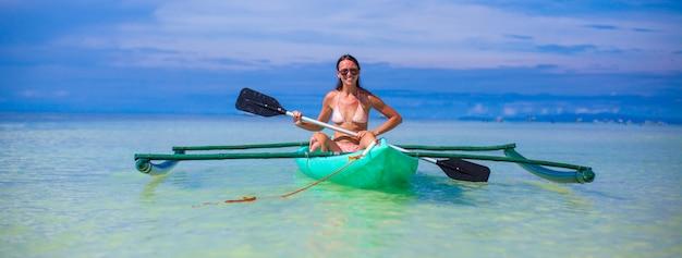 Junge frau, die allein im klaren blauen meer kayak fährt