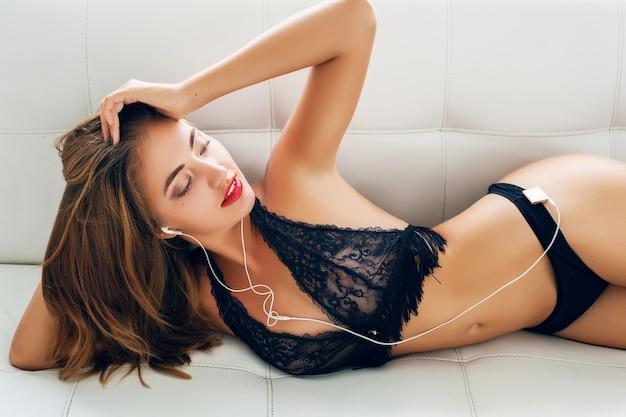 Junge frau, die allein in schwarzen verführerischen dessous auf weißem sofa in tropischer villa liegt und musik auf spieler in kopfhörern lächelnd hört