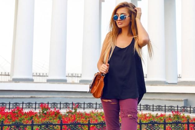 Junge frau, die allein nach dem einkaufen auf der straße am schönen tag geht und stilvolle freizeitkleidung und sonnenbrille trägt.