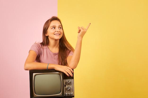 Junge frau, die alten retro-fernseher hält, der gegen gelben und rosa hintergrund sitzt, der mit finger zur seite zeigt