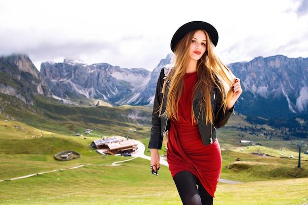 Junge frau, die am alpengebirge aufwirft, kleid, lederjacke, sonnenbrille und rucksack tragend