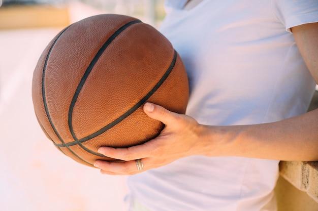 Junge frau, die am basketballplatz steht