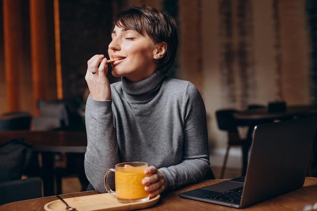 Junge frau, die am computer arbeitet und heißen tee trinkt