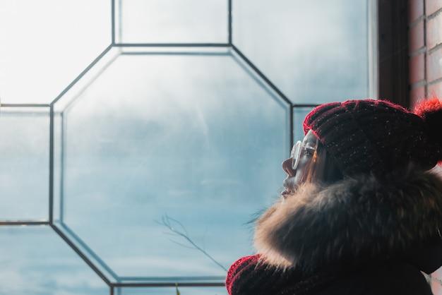 Junge frau, die am fenster sitzt und gefrorenes glas betrachtet.