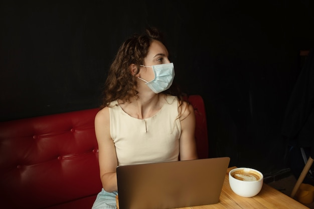 Junge frau, die am kaffeehaus sitzt und am laptop mit gesichtsmaske arbeitet