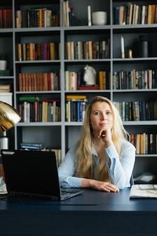 Junge frau, die am laptop auf dem tisch arbeitet. hausaufgaben. studium und ausbildung. mädchen, geschäftsfrau