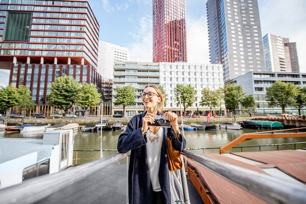 Junge frau, die am modernen hafen mit wolkenkratzern im hintergrund in rotterdam-stadt reist