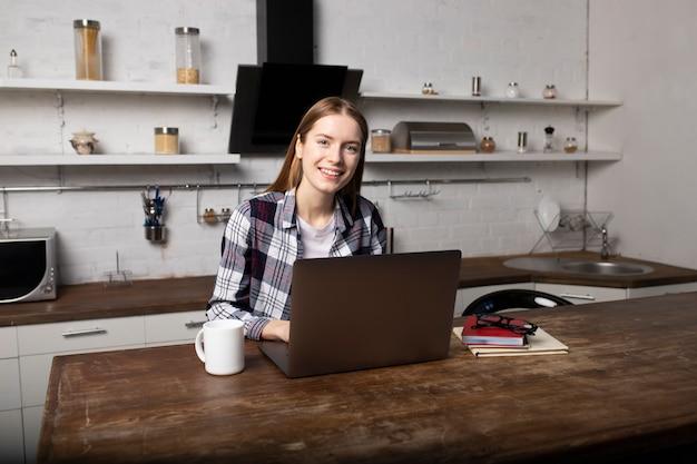 Junge frau, die am morgen zu hause arbeitet. mädchen, das kaffee trinkt. sie benutzt ihren laptop