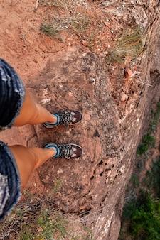 Junge frau, die am rand des berg-, reise- und wanderkonzepts steht