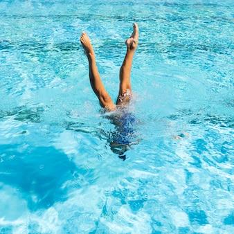 Junge frau, die am schwimmbad aufwirft