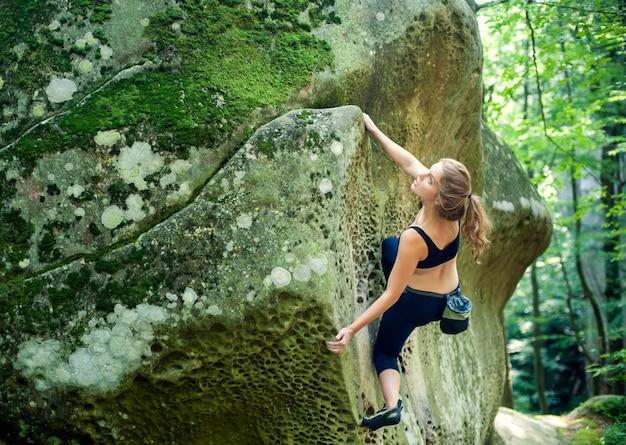 Junge frau, die am sommertag der großen flusssteine im freien klettert