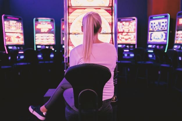 Junge frau, die am spielautomaten im kasino spielt