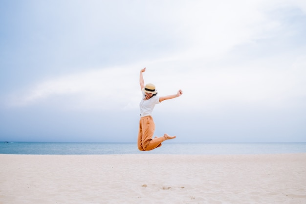 Junge frau, die am strand an den sommerferien springt
