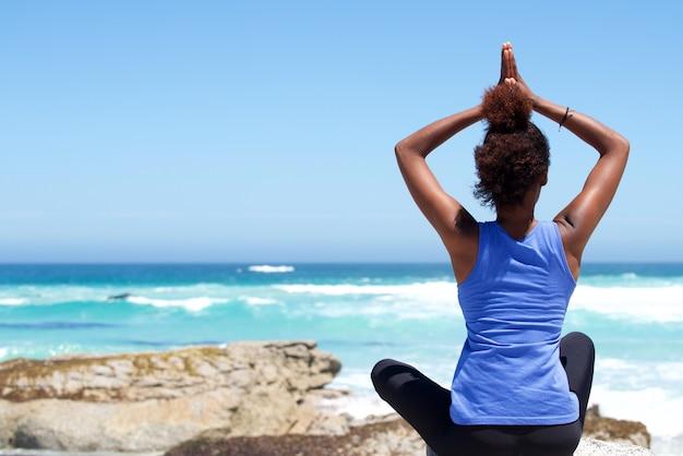 Junge frau, die am strand in der yogahaltung sitzt