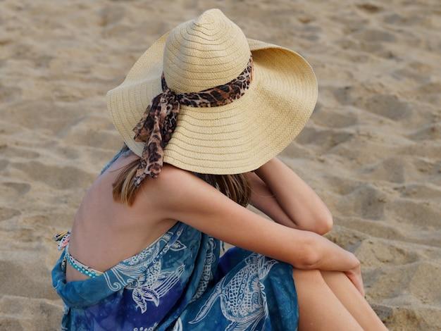 Junge frau, die am strand sitzt, frau im hut, der ozean betrachtet.