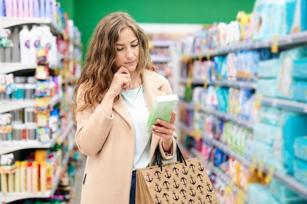 Junge frau, die am supermarkt einkauft und informationen auf einer schachtel liest. wirtschaftliche und nützliche einkäufe.