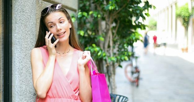 Junge frau, die am telefon beim einkauf in einer stadt spricht