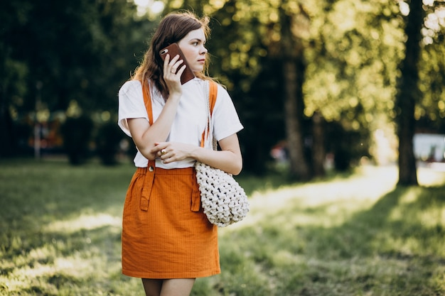 Junge frau, die am telefon im park spricht