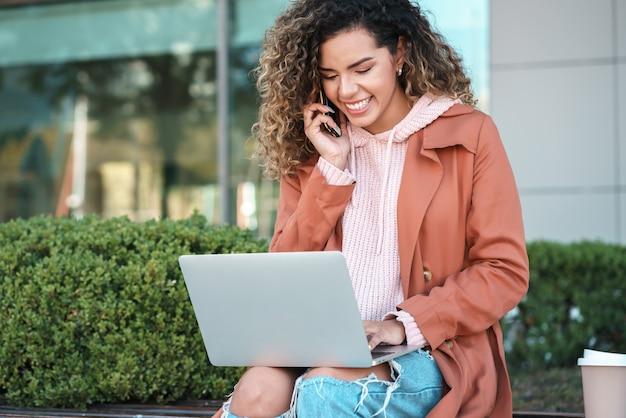 Junge frau, die am telefon spricht und einen laptop benutzt, während sie draußen auf der straße sitzt. urbanes konzept.