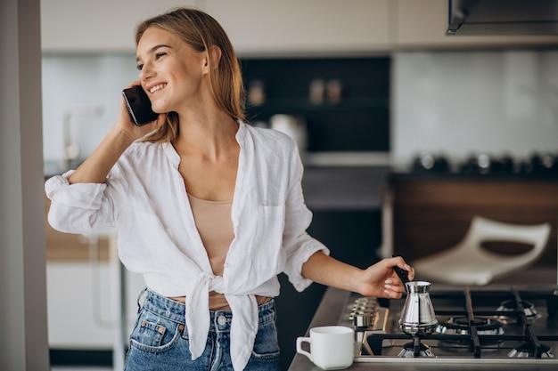 Junge frau, die am telefon spricht und morgenkaffee kocht