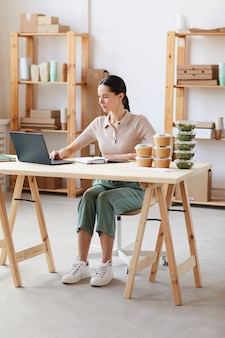 Junge frau, die am tisch mit kisten mit lebensmitteln sitzt und einen laptop benutzt, macht eine lieferung im büro